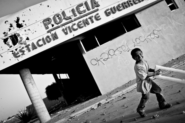 La inocencia de un niño que juega frente a lo que queda de la estación de Policía de Vicente Guerrero, en el valle de San Quintín, lugar de violentos enfrentamientos entre jornaleros y policías el 9 de mayo de 2015.