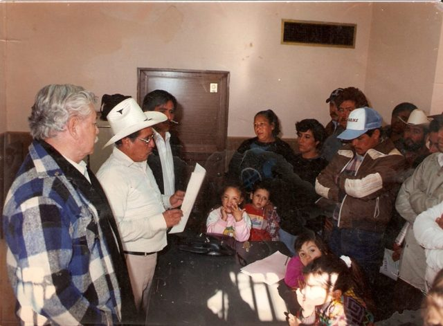Zaqueo Villegas al centro de la imagen, en primer plano el Profr. Antonio Becerra Gaytán, destacado lider de la izquierda chihuahuense, al fondo su hijo Gerardo Villegas en una asamblea de colonos.
