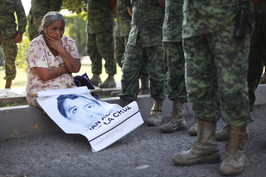 A woman who identified herself as the mother of missing student Adan Abarajan de la Cruz, 23, sits next to Mexican army soldiers standing in front of the entrance to the 27th Infantry Battalion base in Iguala, Mexico, Thursday, Dec. 18, 2014. Relatives of the 43 missing students blocked the entrance to the base in protest over the army's alleged responsibility or lack of response during the night of Sept. 26 when 43 students were taken by municipal police and then handed over to a drug gang to be killed and then the bodies burned, according to the results of the Attorney General's investigation. (AP Photo/Felix Marquez)