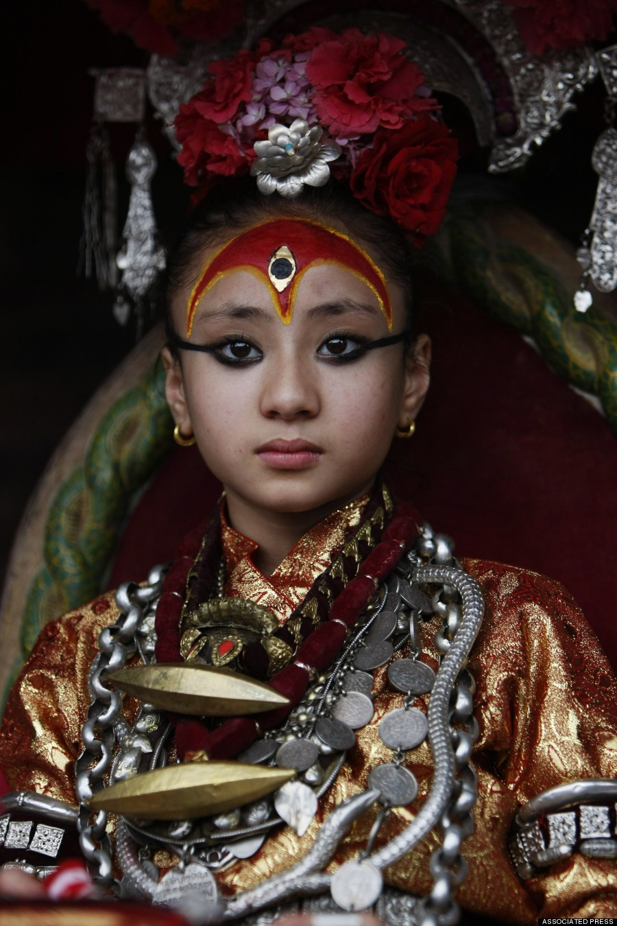 Nepal's living goddess locally known as Kumari, Samita Bajracharya, watches the last day of Rato Machhendranath chariot festival in Patan, outskirts of Katmandu, Nepal, Sunday, June 24, 2012. Kumari, meaning virgin in Nepalese, are young pre-pubescent girls and are considered by devotees to be incarnations of a Hindu goddess. Selected as toddlers, living goddesses usually keep their positions until they reach puberty. (AP Photo/Binod Joshi)