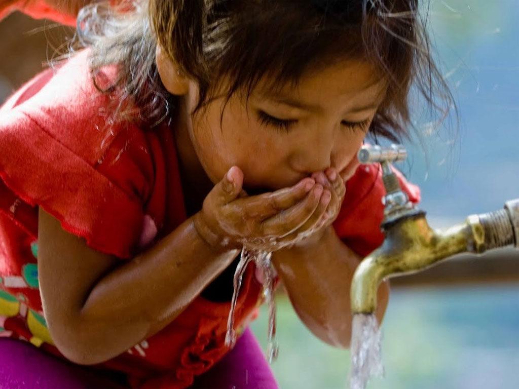 nina-pobre-bebe-agua-llave